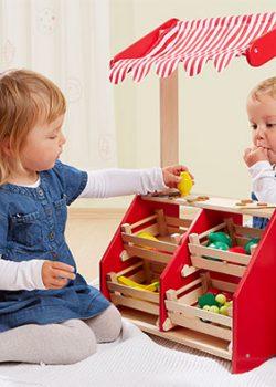 Kinder spielen mit Holz Kaufmannsladen