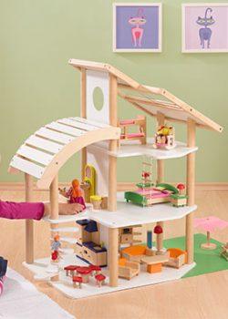 Mädchen spielt mit Holz Puppenhaus