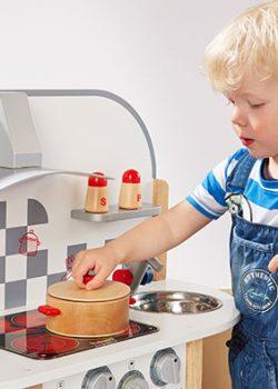 Junge spielt mit Holz Spielküche