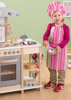 Mädchen in der Spielküche aus Holz
