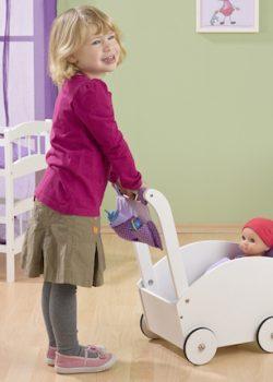 Kind schiebt Puppe im Holz Kinderwagen