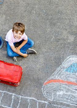 Kind sitzt mit Koffern auf bemalter Straße