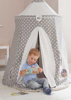 Kind liest Buch im Spielzelt