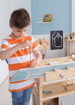 Junge spielt mit Holz Werkbank