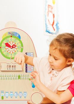 Mädchen lernt Uhrzeit mit Holz Lernuhr